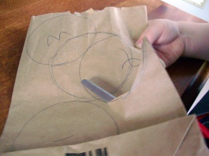 Cut threw all layers of the paper bag, and make a pile of circles.  (1 bag = 1 flower)  By cutting close to the edge, you should get three circles from each cut. (The third comes from the fold)