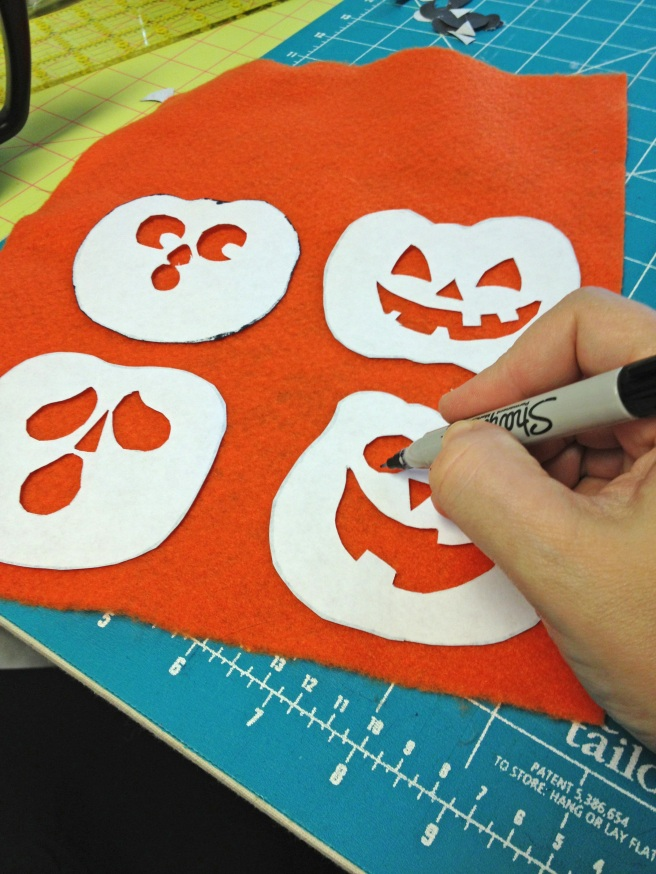 Place pumpkin templates FACE DOWN on orange felt and outline pumpkins and faces with marker. This will be the wrong side of the pumpkins, and ink won't show on other side.