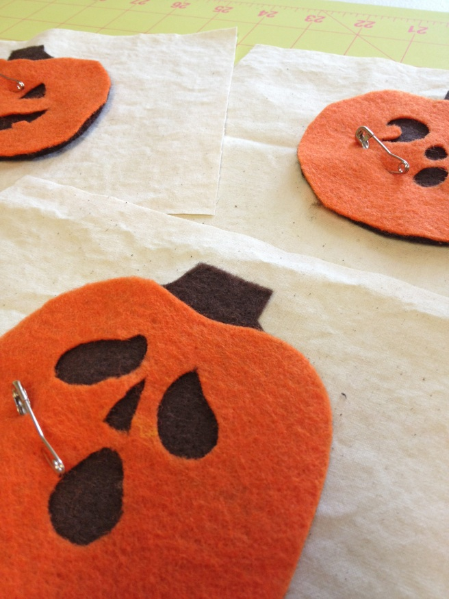 """Pin pumpkins to the cream rectangles as shown, 5.5"""" edges on the side."""