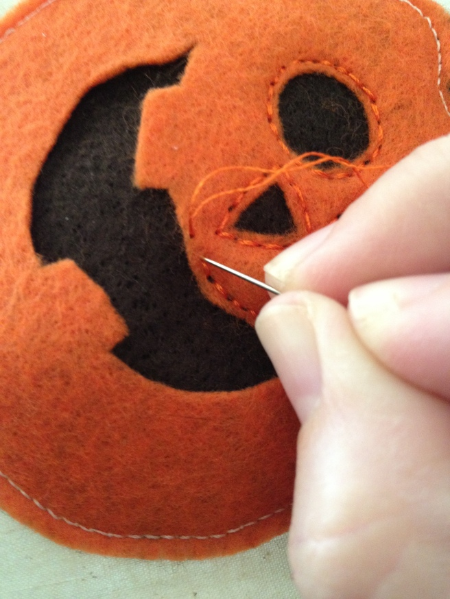 Hand stitch faces with a backstitch. You can use the sewing machine, if you're brave, by I advise against it, since some of the facial features are small.